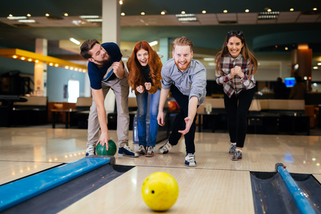 casually: Friends bowling at club and having fun playing casually Stock Photo
