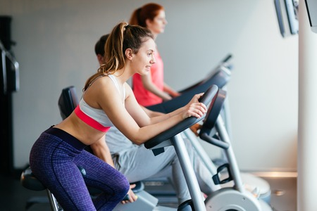 cardio workout: People traning in gym on various machines as part of cardio workout