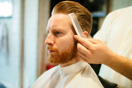 Combing of hair and styling in barber shop Banco de Imagens