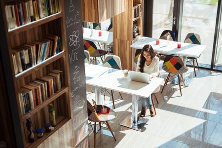 cafe internet: Hermosa morena estudiar en el cuaderno