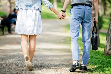 holding hands while walking: Couple of people holding hands while walking in park