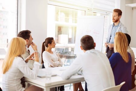 explained: Business plan explained on flipchart by CEO to employees Stock Photo