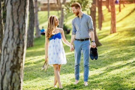 Couple enjoying romantic walk in nature barefoot