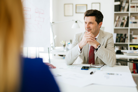 company director: Company director sitting at table thinking about future plans