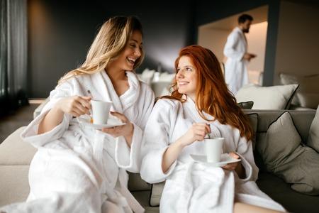 Mujeres que se relajan y que beben el té de ropas durante el fin de semana de bienestar