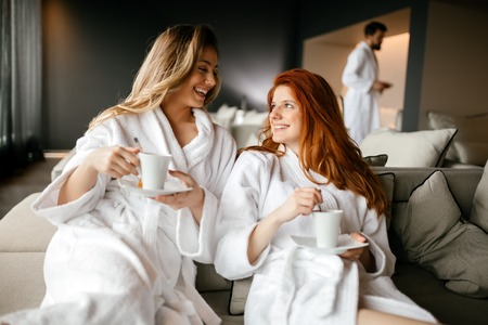 Vrouwen ontspannen en het drinken van thee in gewaden tijdens wellnessweekend
