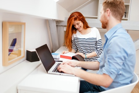 Husband and wife working from home on laptop
