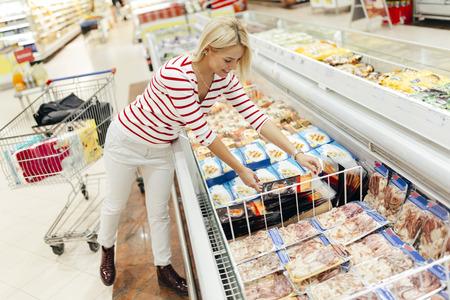 Bella donna shopping e la scelta di cibo in supermercato Archivio Fotografico - 56794348