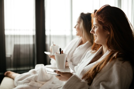 bathrobes: Women in bathrobes enjoying tea during wellness weekend