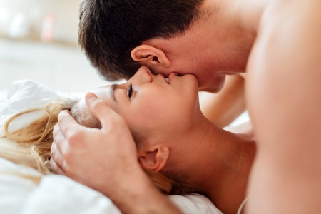 sex tenderness: Sensual foreplay by couple in bedroom Stock Photo