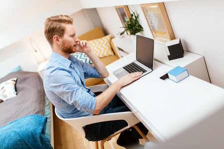 selfemployed: Handsome self-employed business working from home on a laptop Stock Photo