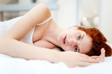 inocent: Beautiful red haired woman lying on bed looking pure and inocent Stock Photo