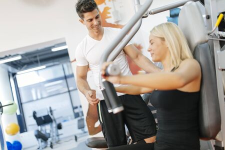 Beautiful woman exercising in gym with some help by personal trainer
