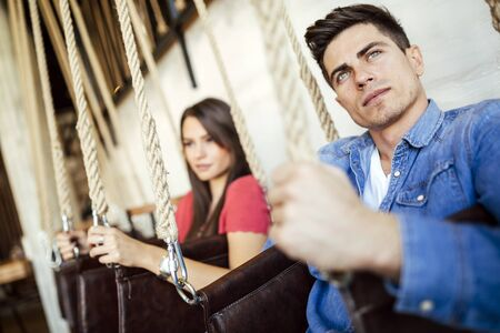 clinical psychology: Portrait of couple sitting in swings posing Stock Photo