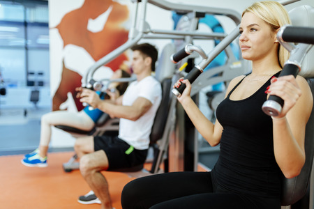 Las personas que ejercitan en gimnasia en las máquinas Vaus