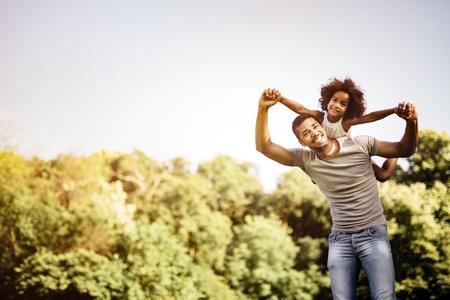 Father carrying daughter piggyback and being truly happy Stock Photo