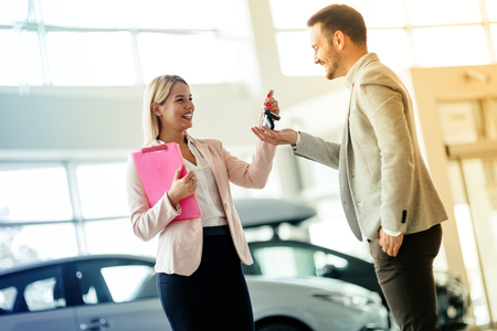 bought: Happy customer just bought a car at car dealership Stock Photo