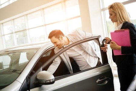 selling service smile: Salesperson showing vehicle to potential customer in dealership Stock Photo
