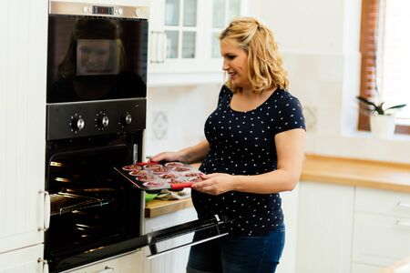 woman baking: Beautiful pregnant woman baking muffins in kitchen Stock Photo