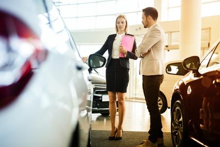 salesperson: Car salesperson assisting customer at car dealership Stock Photo