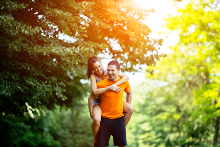 man carrying woman: Man carrying woman piggyback after jogging is done