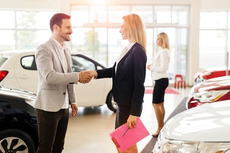 salesperson: Customer looking at cars at dealership and talking to salesperson