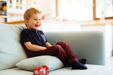 living room sofa: Happy boy sitting on sofa in living room