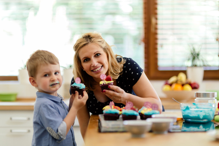 joyfully: Mother and child joyfully eating muffins just made by them