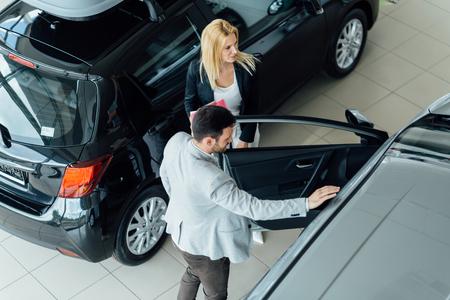 salesperson: Elegant salesperson working at car dealership