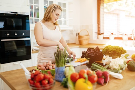 Pregnant woman making a meal in kitchen from fresh ingredients