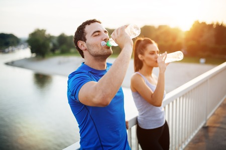 staying: Couple staying hydrated after workout