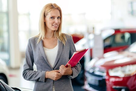 saleswoman: Professional saleswoman working at car dealership