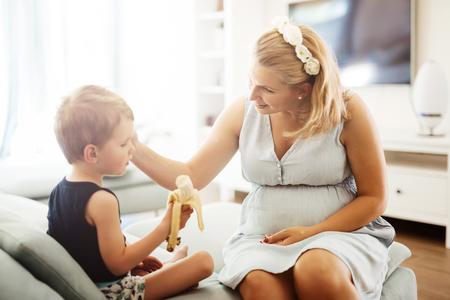 earing: Beautiful mother cuddling child while earing a banana