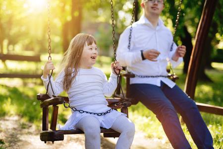 Gelukkig kind met het syndroom van Down te genieten van swing op speelplaats