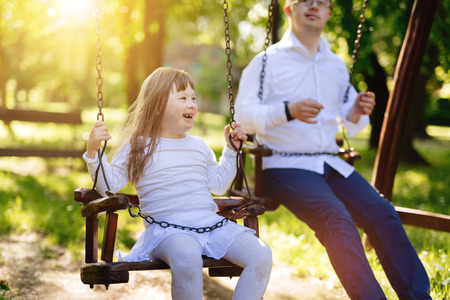 Happy child with down syndrome enjoying swing on playground