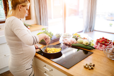 Beautiful pregnant woman preparing meal on kitchen island from fresh ingredients