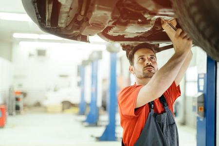 Car mechanic upkeeping car in dealership garage Zdjęcie Seryjne
