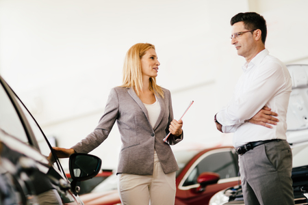 salesperson: Salesperson showing vehicle to potential customer in dealership Stock Photo