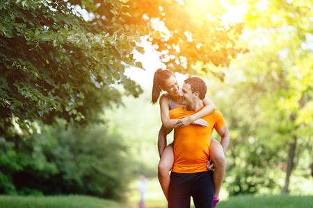 carrying girl: Guy carrying girl piggyback after jogging