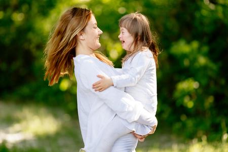 Baby met neer sydrome genieten van buiten spelen met zus Stockfoto