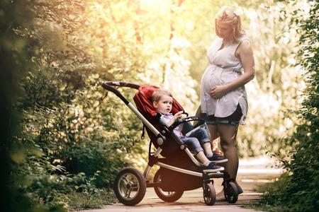 niño empujando: mujer embarazada con su niño en el cochecito de niño caminando en la naturaleza Foto de archivo