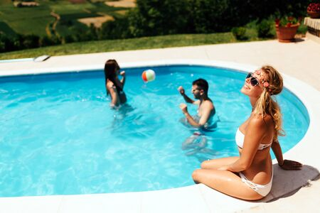 pool side: Woman enjoying summer at pool side during summer Stock Photo
