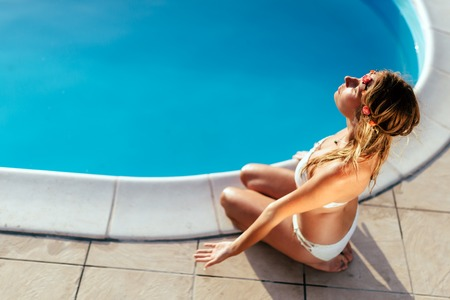 body scape: Beautiful blond woman meditating at pool