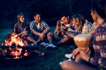 밤에는 모닥불 근처에서 음악을 즐기는 친구들 스톡 콘텐츠
