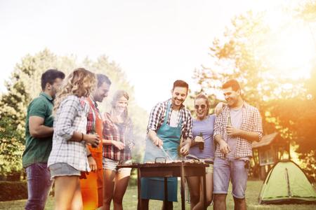 Vrienden kamperen en barbecueën in de natuur