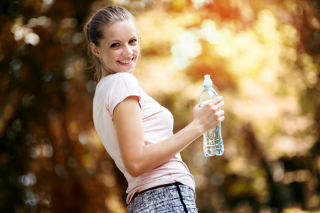 jogger: Dehydrated female jogger drinking water