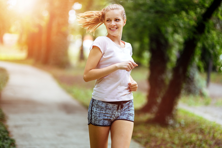 Beautiful athletic  female jogger in nature Stock Photo