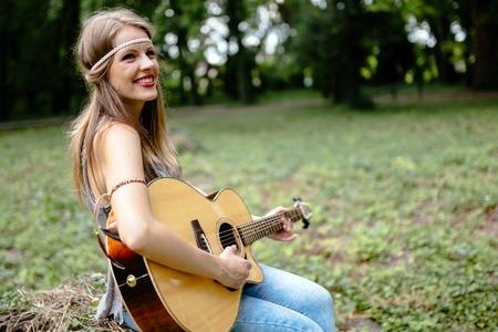 hippie girl: Beautiful hippie girl playing guitar in nature