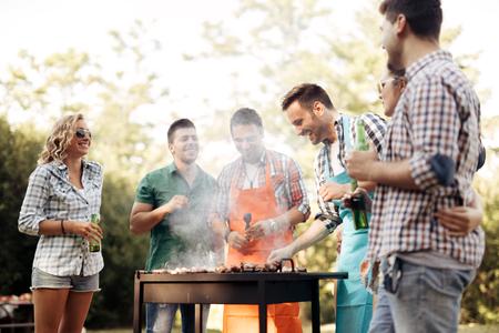 친구 캠핑과 자연 속에서 바베큐를 갖는