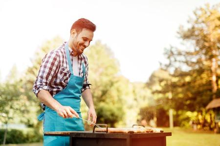 ハンサムな男性が屋外バーベキューを準備します。